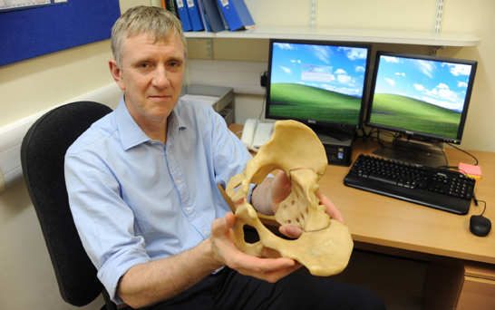 Surgeon Craig Gerrand with model of pelvis